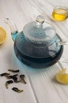 Chá azul no bule de vidro na superfície branca