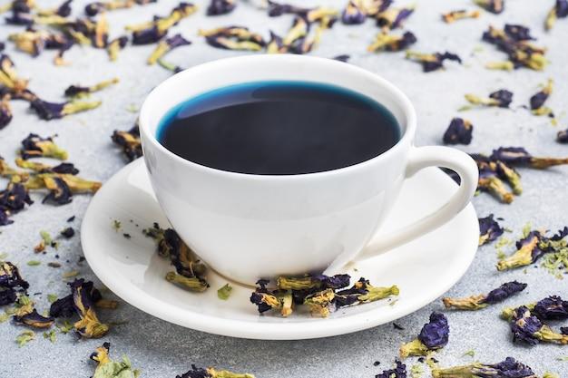Chá azul tailandês anchan de botões klitoria ternate em uma xícara branca.