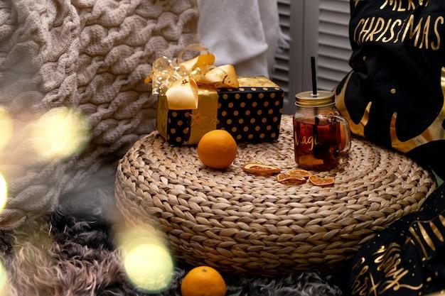 Chá beber em uma caneca com um tubo perto da cama lindamente caixa embalada com um presente. quarto quarto rozhdestrenka noite. fundo chá da manhã bebendo chá cozido perto da cama. inscrição feliz natal
