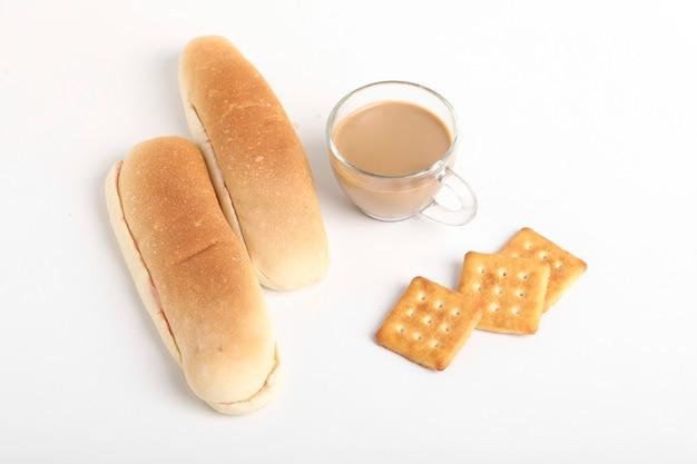 Chá, biscoitos e pãezinhos em superfície de madeira