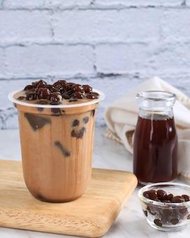 Chá boba / bubble. chá com leite caseiro com pérolas em fundo de madeira. adicione com açúcar de palma líquido
