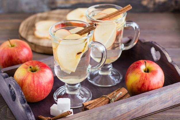 Chá calmante quente feito de maçãs e canela em copos e ingredientes para cozinhar em uma mesa de madeira. conceito de desintoxicação, antidepressivo