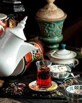 Chá chá preto com uma fatia de manjar turco de limão e flores secas