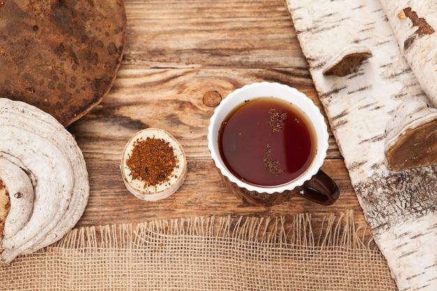 Chá chaga em uma xícara na mesa de madeira. estilo rústico.