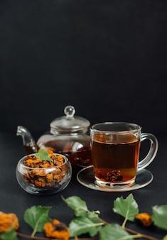 Chá chaga orgânico em um fundo preto. infusão com cogumelo de bétula em uma xícara de vidro e bule. bebida saudável. orientação vertical. copie o espaço.