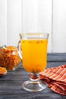 Chá colorido quente de espinheiro-mar natural em um copo de vidro com frutas frescas cruas e pau de canela