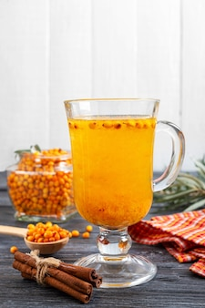 Chá colorido quente de espinheiro-mar natural em uma xícara de vidro com frutas frescas e cruas e paus de canela