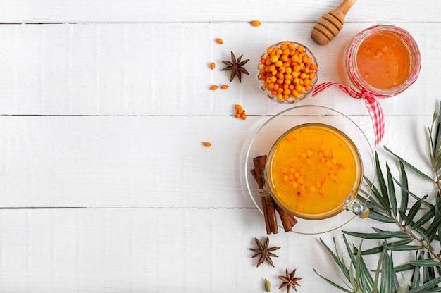Chá colorido quente de espinheiro-mar natural em uma xícara de vidro conceito de bebidas quentes sazonais vista superior