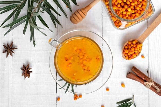 Chá colorido quente de espinheiro-mar natural em uma xícara de vidro conceito de bebidas quentes sazonais