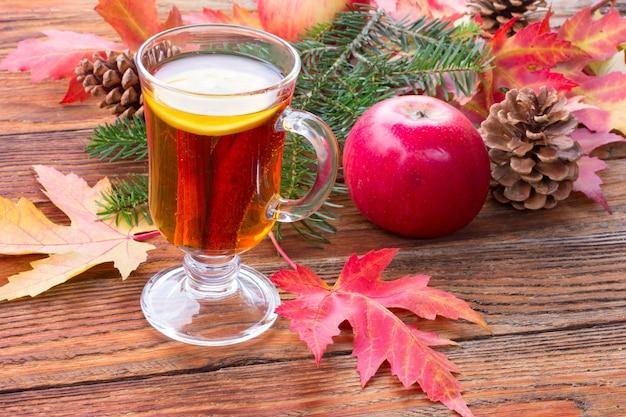 Chá com canela e limão, maçãs maduras, folhas vermelhas de outono