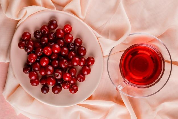 Chá com cerejas em uma caneca de vidro na cor rosa e têxtil.