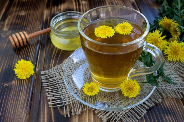 Chá com dente de leão na xícara de vidro na superfície de madeira rústica