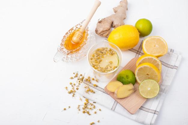 Chá com ervas, limão e gengibre no fundo branco e mel