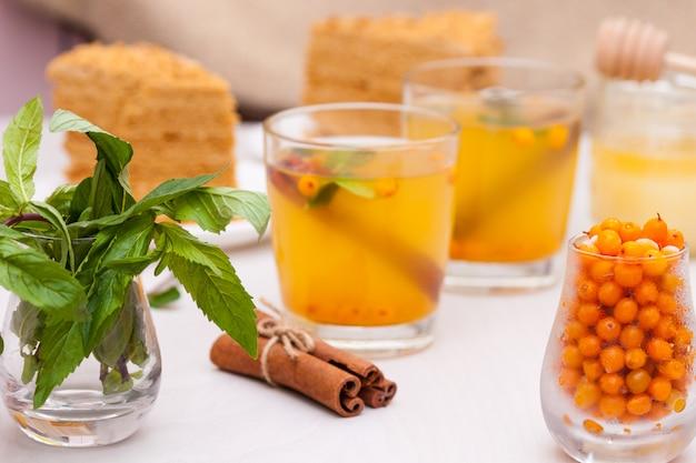 Chá com espinheiro, menta, mel, canela e bolo em camadas de mel