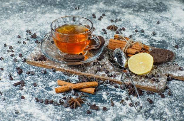 Chá com farinha, chips de chocolate, biscoitos, especiarias, limão em uma caneca no concreto e na tábua, vista de alto ângulo.