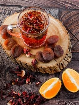 Chá com frutas secas, ervas, laranja, madeira em um copo na superfície da telha de pedra