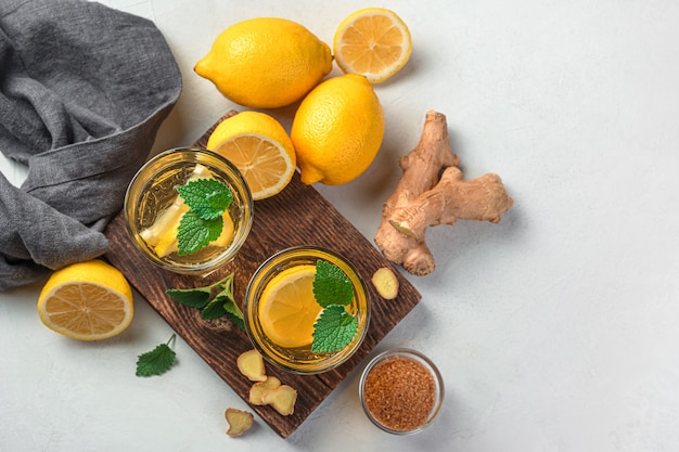 Chá com gengibre e limão em um fundo cinza claro. vista superior, copie o espaço.