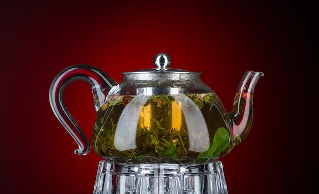 Chá com hortelã e ervas em um bule transparente sobre fundo vermelho. isolado com luz de fundo