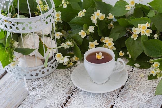Chá com jasmim e marshmallows em uma gaiola decorativa branca sobre uma mesa de madeira branca