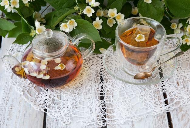 Chá com jasmim e um bule transparente com chá em uma mesa de madeira branca