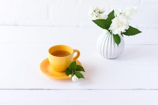Chá com jasmim em uma xícara amarela com um cheiro perfumado de espiões de flores de jasmim. pação saudável.