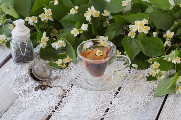 Chá com jasmim, um pote de chá verde e uma máquina de chá para chá em uma mesa de madeira branca