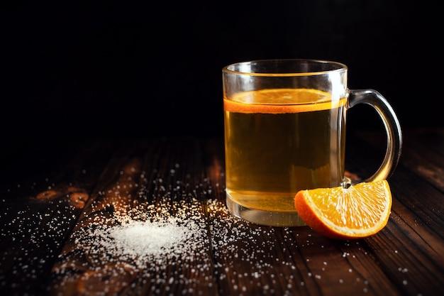 Chá com laranja polvilhada com açúcar em fatias de laranja