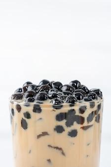 Chá com leite bolha com cobertura de pérola de tapioca, famosa bebida taiwanesa em mesa de madeira branca