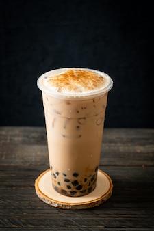 Chá com leite de taiwan com bolha e queijo queimado na mesa de madeira