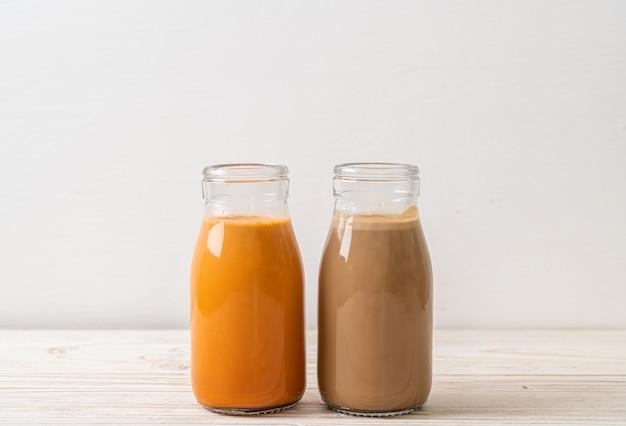 Chá com leite tailandês e café com leite em garrafa na mesa de madeira