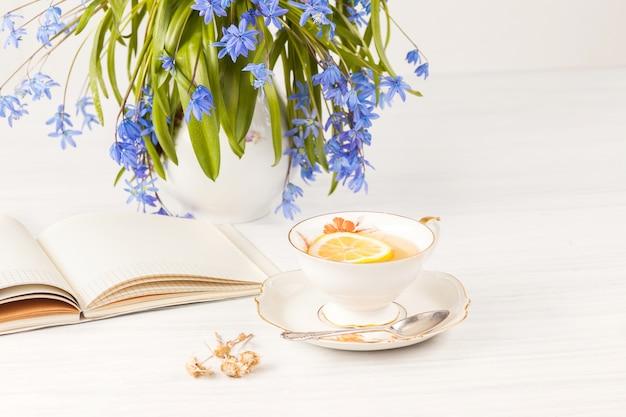 Chá com limão e buquê de prímulas azuis em cima da mesa