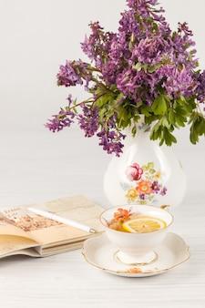 Chá com limão e buquê de prímulas lilás em cima da mesa