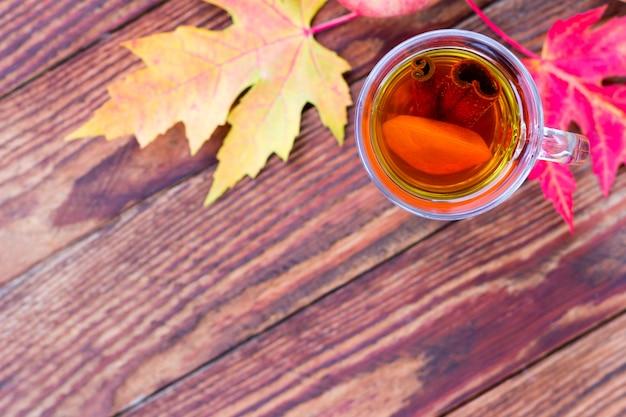 Chá com limão e canela em um copo e folhas vermelhas de outono