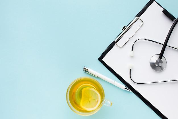 Chá com limão e estetoscópio no bloco de notas