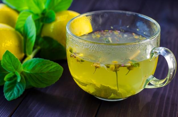 Chá com limão e hortelã em copo de vidro transparente sobre a mesa