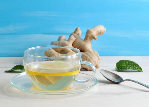 Chá com limão e hortelã em um recipiente de vidro no fundo