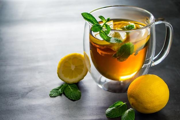 Chá com limão e hortelã em uma xícara transparente.