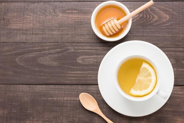 Chá com limão e mel no fundo de madeira