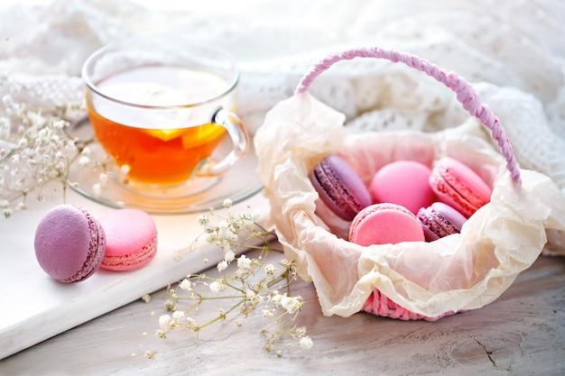 Chá com limão, flores silvestres e macaron na mesa de madeira branca.