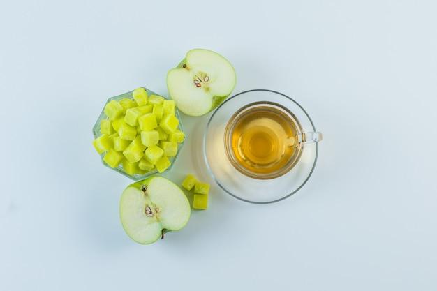 Chá com maçã, cubos de açúcar em uma caneca em fundo branco, plano leigo.