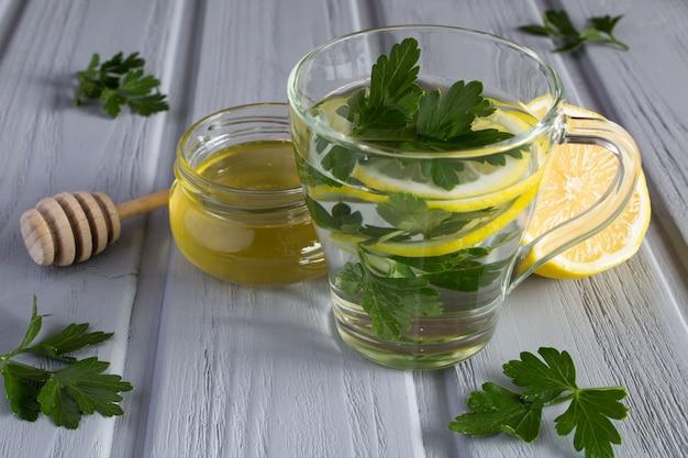 Chá com salsa, mel e limão na superfície cinza de madeira