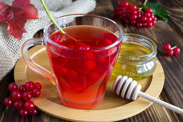 Chá com viburnum e mel no fundo rústico