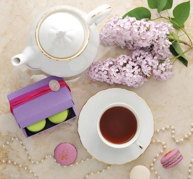 Chá da manhã com biscoitos, macarons e um ramo de lilás