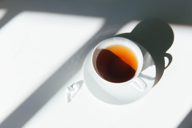Chá da manhã em uma mesa branca com fones de ouvido brancos. manhã limpa, tranquila e calma