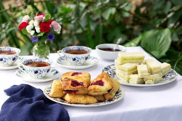 Chá da tarde no jardim com scones, geléia de morango, sanduíches com pepino e salada de ovo.