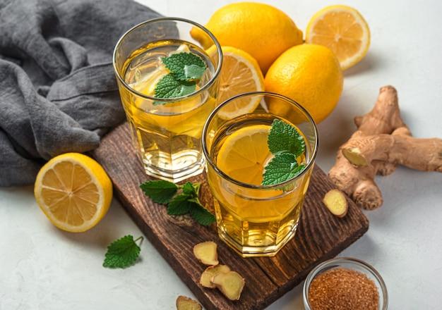Chá de aquecimento com limão e gengibre em dois copos em um fundo cinza. fechar-se.