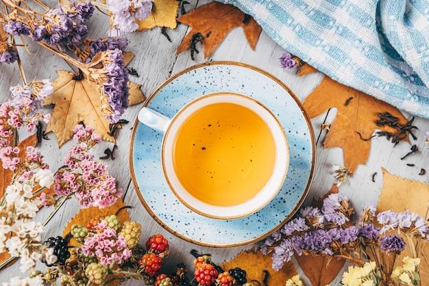 Chá de aquecimento outono em uma mesa de madeira com folhas de árvore de outono nas proximidades