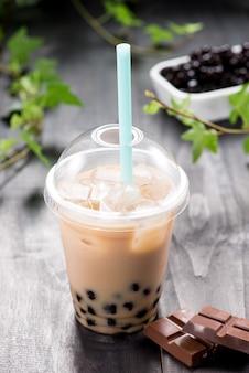 Chá de bolha de leite com chocolate caseiro em copos plásticos na mesa.