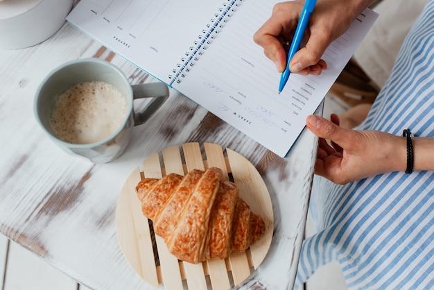 Chá de bolo folhado de café da manhã empresarial e caderno com caneta sobre a mesa de negócios
