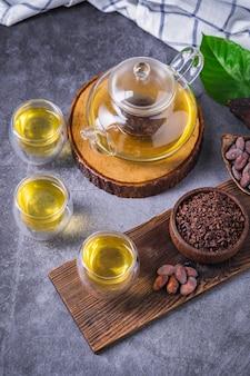Chá de cacau quente. chá de ervas com chocolate quente fresco, feito de flocos de cacau, rico em flavonóides e antioxidantes, servido em copos, foco diferencial